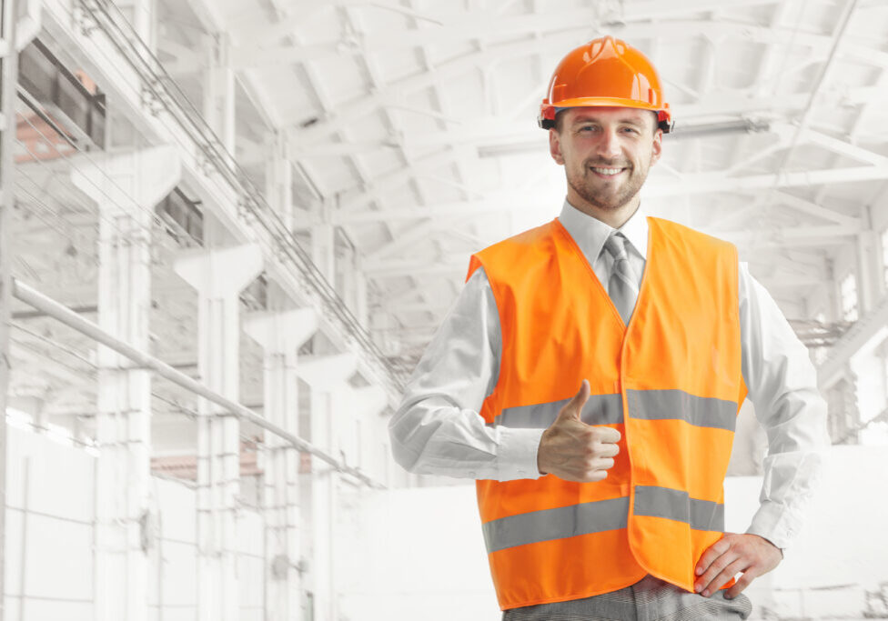 The builder in a construction vest and orange helmet smiling with sign ok against industrial background. Safety specialist, engineer, industry, architecture, manager, occupation, businessman, job concept